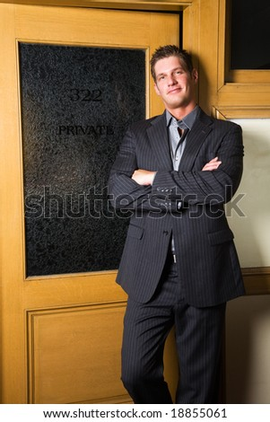 A happy caucasian businessman standing outside of his office