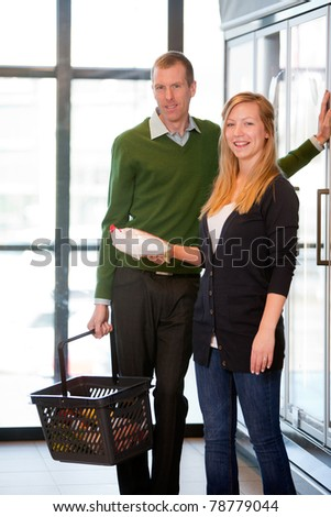 A happy caucasian couple buying grocers in a supermarket frozen section - stock photo