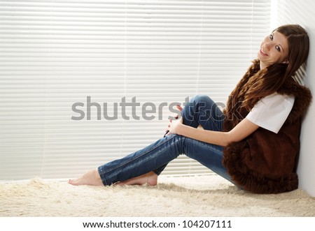 A happy caucasian woman sitting on the carpet against the window