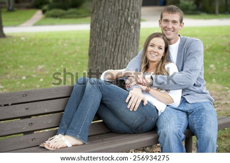 A happy caucasian young couple sitting on a bench at the park. - stock photo