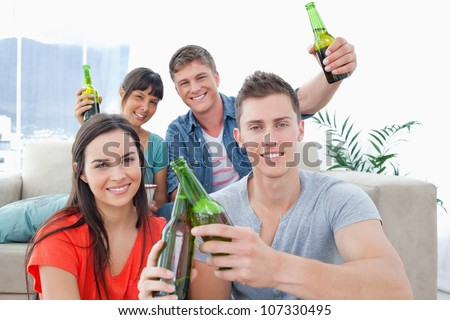 A happy celebrating group of friends raising and clinking bottles in happiness - stock photo