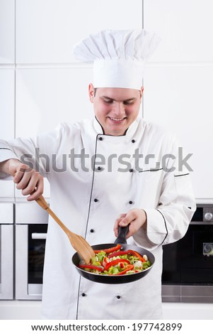 A happy ched frying veggies on a pan