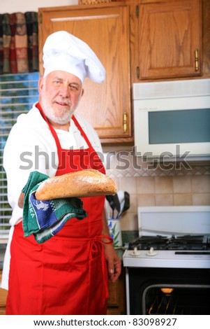 a happy chef prepares one of his famous dishes for someone while in his kitchen at a world famous bed and breakfast hotel restaurant. - stock photo