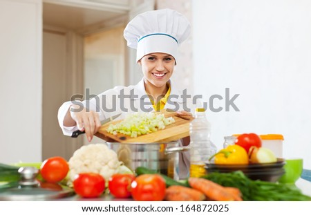 A happy chef works with vegetables in a commercial kitchen. - stock photo