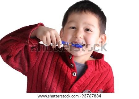 A happy child boy is brushing his teeth, looking camera in the studio and smiling - stock photo