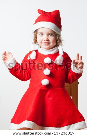 A happy child with Christmas joy dressed as Santa Claus