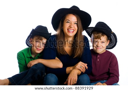 A happy, country family with cowboy hats.  Cute boys and a pretty Mom. - stock photo