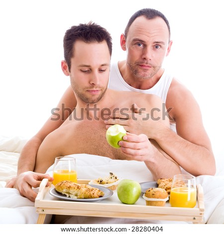 A Happy couple and their breakfast on a tray in bed - stock photo