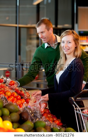 A happy couple buying fruit and vegetables in a supermarket - stock photo
