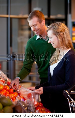 A happy couple buying fruit in a supermarket - shallow depth of field with sharp focus on woman - stock photo