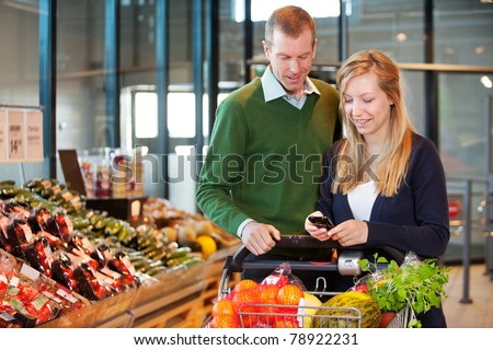A happy couple buying groceries looking at grocery list on phone - stock photo