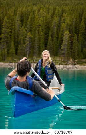 A happy couple canoeing on a glacial lake