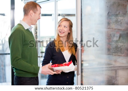 A happy couple choosing groceries from the frozen food section in a supermarket - stock photo