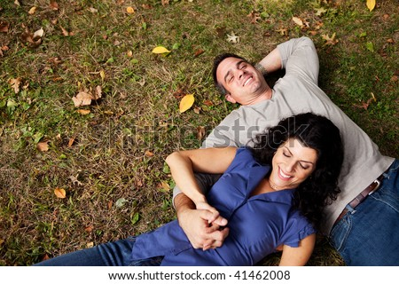 A happy couple daydreaming in a park on grass - sharp focus on man - stock photo