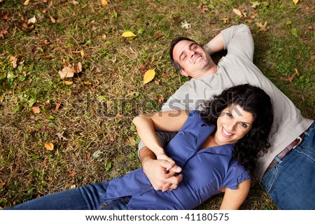 A happy couple daydreaming in a park on grass - sharp focus on woman - stock photo
