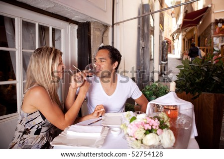A happy couple drinking wine in a cafe in France - stock photo