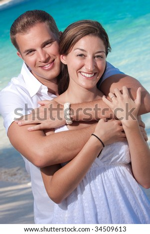 a happy couple embraces on the beach