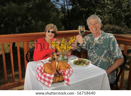 A happy couple enjoying a healthy lunch outside on their deck. - stock photo