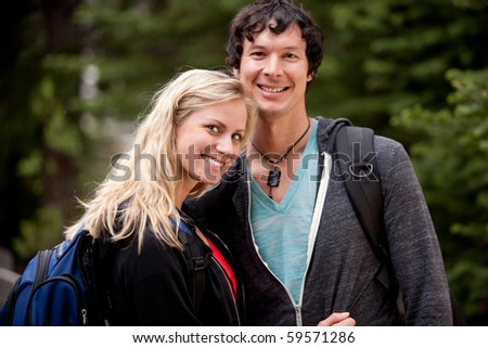 A happy couple hiking in the forest - stock photo