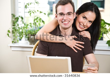 A happy couple holding a credit card shopping online
