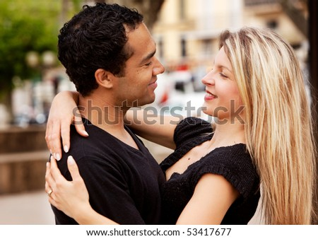 A happy couple holding and looking at eachother. - stock photo