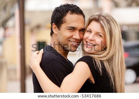 A happy couple hugging and looking at the camera - stock photo