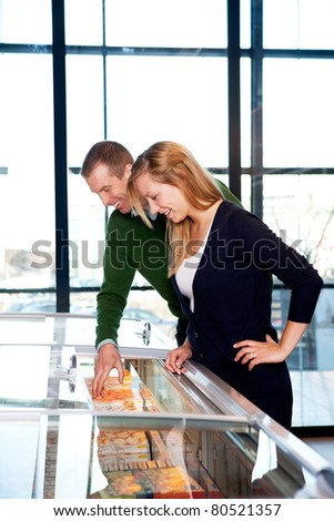 A happy couple in a supermarket buying frozen food - stock photo
