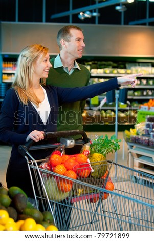 A happy couple in a supermarket buying groceries - stock photo