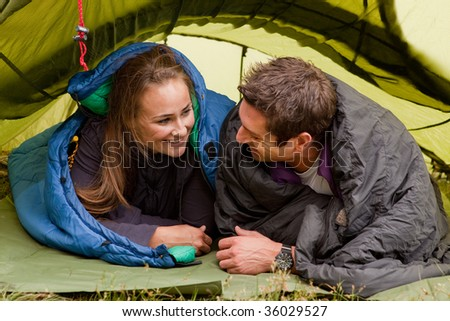 A happy couple in a tent looking at each other