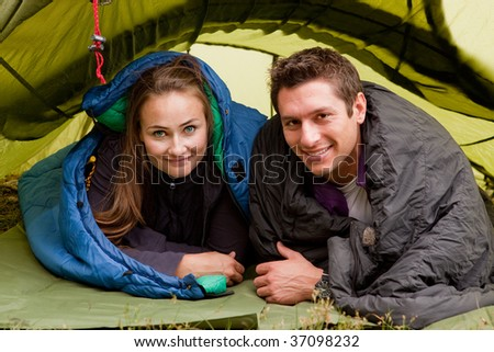 A happy couple in a tent looking at the camera - stock photo