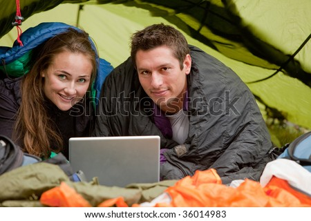A happy couple in a tent using a computer looking at the camera - stock photo