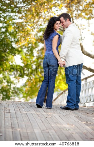 A happy couple in love walking on a bridge - stock photo