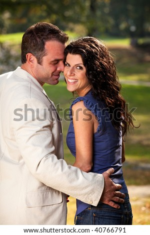 A happy couple in the park having fun on a warm day - stock photo
