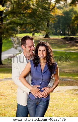 A happy couple in the park hugging - stock photo