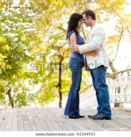 A happy couple in the park looking at the camera and hugging - stock photo