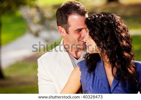 A happy couple in the park sharing a hug and kiss - stock photo