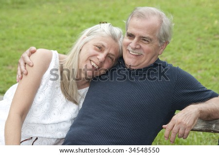 A happy couple in their early retirement years relaxes outdoors. - stock photo