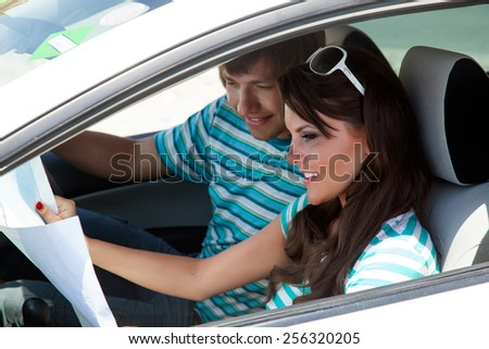 A happy couple is going on a car trip - stock photo