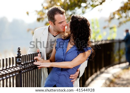 A happy couple kissing in the park on a beautiful day - stock photo