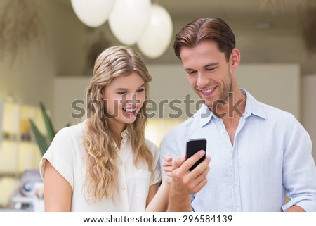 A happy couple looking at smartphone at the mall