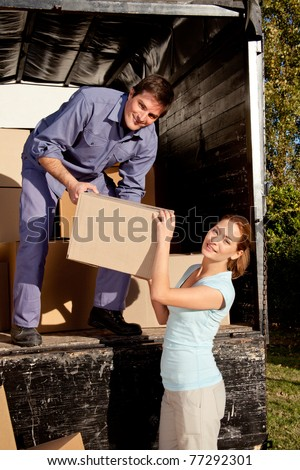 A happy couple moving boxes from a moving truck - stock photo