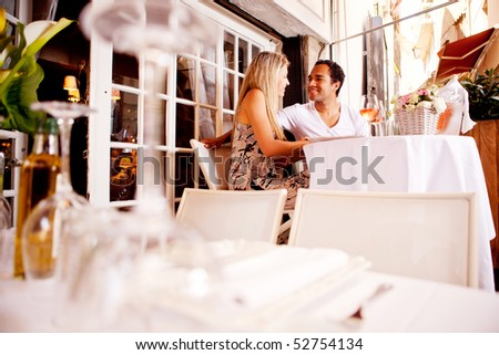 A happy couple on a date in an outdoor restaurant