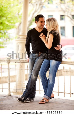 A happy couple on vacation in an urban setting - stock photo