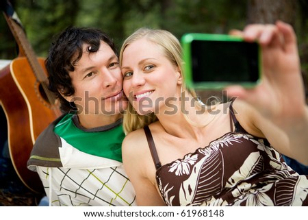 A happy couple outdoors taking a self portrait with a camera phone - stock photo