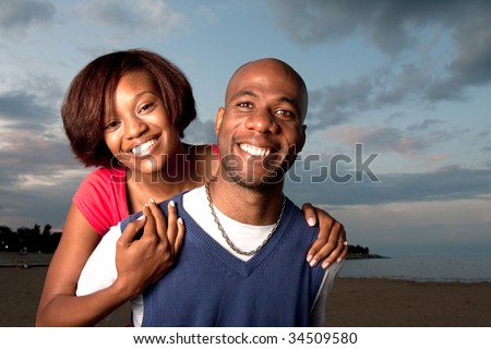 a happy couple poses together at dusk - stock photo