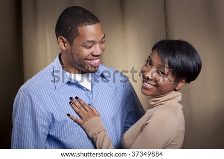 a happy couple poses together in front of a neutral background