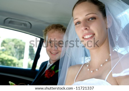 A happy couple recently married - in the back seat of the wedding car - stock photo