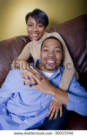 a happy couple relaxes on the couch