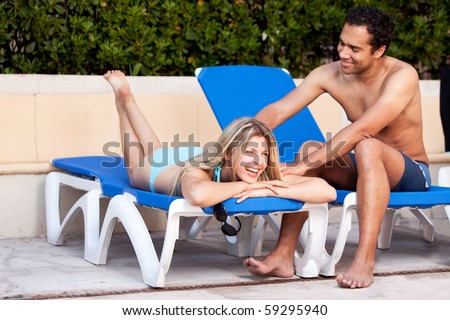 A happy couple relaxing beside a pool. - stock photo