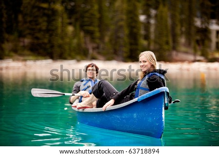 A happy couple relaxing in a canoe on a glacial lake - stock photo
